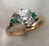 14Kt yellow gold 'Elizabeth' set with a 1.0ct round diamond and two side .12ct round emeralds.