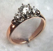 14kt rose gold 'Laura' set with a .60ct round brilliant cut diamond and two .15ct side diamonds.