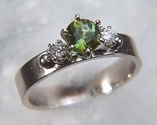 14kt white gold 'Laura' set with a .89ct round green tourmaline and two .10ct side diamonds.