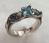 14Kt white gold 'Sarah' Engagement Ring set a 5X5 square blue topaz, two 5X3 pear shaped blue sapphires and two round diamonds.