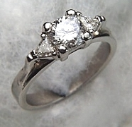 14Kt white gold 'Susan' set with a .50ct round brilliant cut diamond and two 3mm triangle cut diamonds on either side.
