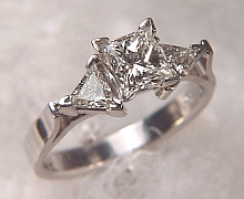 Platinum 'Susan' set with a 1.01ct princess cut diamond and two 4.5mm triangle cut diamonds on either side.